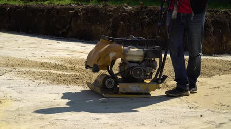 compacto : partial view of worker using vibratory plate compactor at construction site