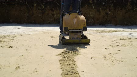compactor : ramming sand with vibratory plate compactor at construction site of new house