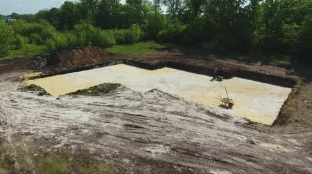 compactor : aerial of man ramming sand with vibratory plate compactor in foundation pit