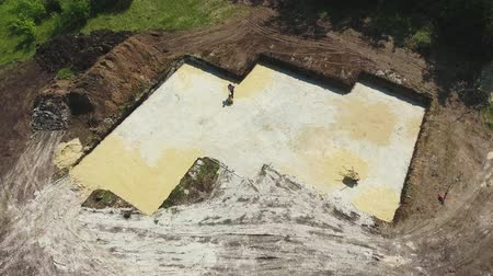 kompakt : aerial of worker with vibratory plate compactor ramming sand in foundation pit