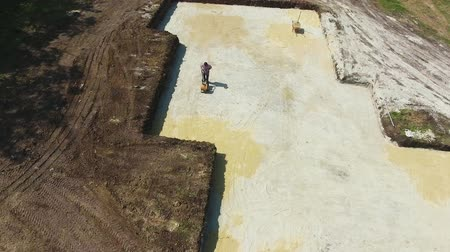 compactor : aerial of preparing foundation by ramming sand with vibratory plate compactor