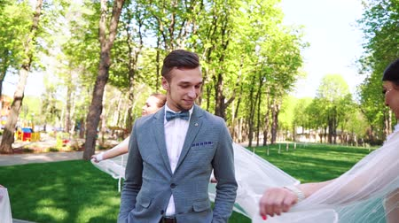 duygusallık : handsome groom looking at beautiful brides walking around him in sunny park
