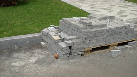 kočičí hlava : pile of new grey paving stones on wooden pallet near walking path and green lawn