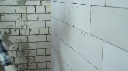 aerated : construction worker screwing in screws into block wall with electric drill