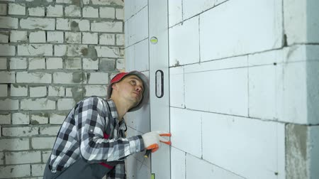 aerated : builder checking evenness of markup lines on block wall with bubble level