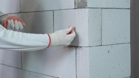 aerated : tilt up shot of worker inserting dowels into holes drilled in block wall Stock Footage