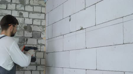 dowel : builder drilling holes in block wall and inserting dowels