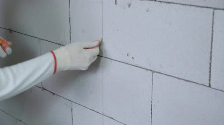 インサート : tilt up shot of builder inserting dowels into drilled holes in block wall