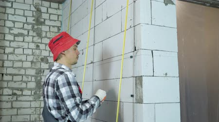 зажим : tilt up shot of builder installing clamps on aerated concrete block wall