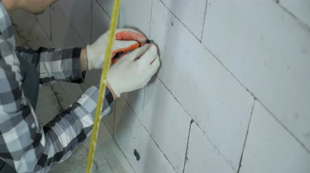 зажим : tilt up shot of construction worker installing clamps on block wall