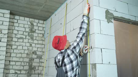 зажим : tilt shot of builder installing metal rails onto clamps on block wall