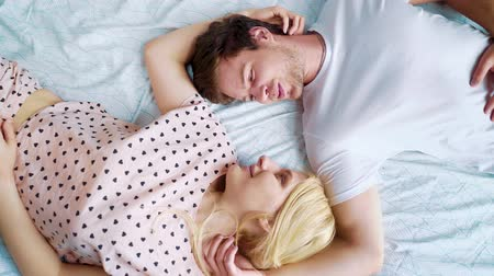 pajama : top down spinning over romantic couple lying in bed face to face in the morning Stock Footage