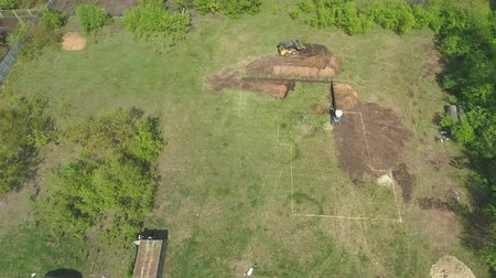 травянистый : aerial of digging foundation pit for new house by mini loader and excavator Стоковые видеозаписи