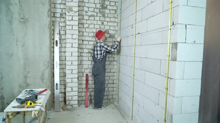 aerated : man in work wear and red cap installs metal rail onto concrete block wall