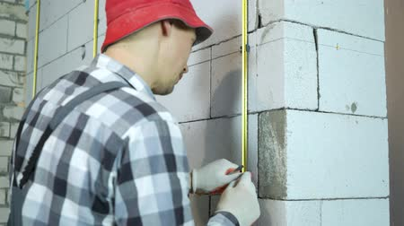 aerated : man in work wear and red cap fixing metal rail with clamps on block wall Stock Footage