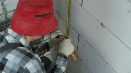 aerated : high angle shot of worker fixing metal rail with clamp on concrete block wall