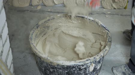 шпатель : cropped shot of builder taking plaster from bucket with putty knife