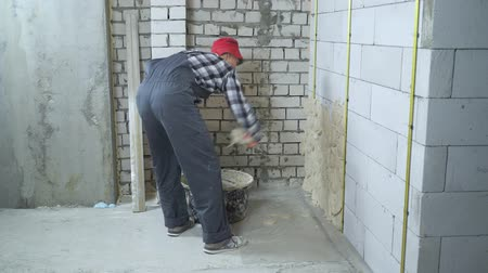 aerated : man in work wear and red cap plastering aerated concrete block wall