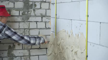 kielnia : cropped shot of builder plastering aerated concrete block wall