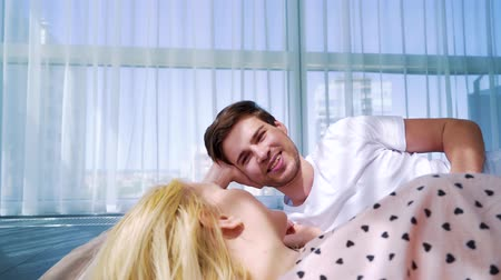 vasárnap : young handsome man lying on floor and smiling to his beloved woman in sunny room