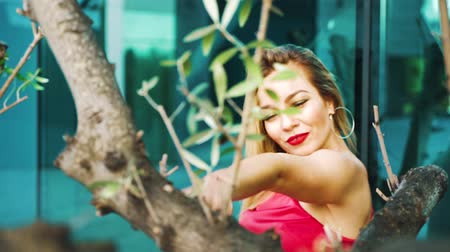 talento : sexy blonde woman dances behind trees in city center in slow motion