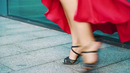highheels : cropped shot of dancing blonde woman in red dress in urban environment Stock Footage