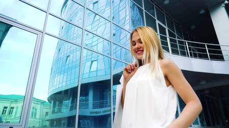 outside : low angle shot of happy blonde woman in stylish outfit passing by mirror surface of skyscraper