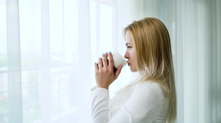домашний интерьер : side view of young blonde woman looking through window and drinking coffee