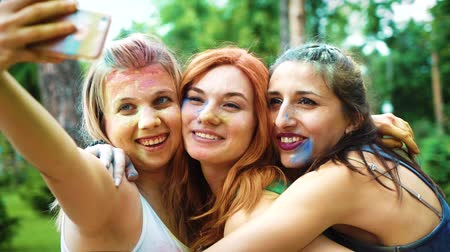 biesiada : joyful girls painted with colorful powder laugh and make selfies after Holi fest