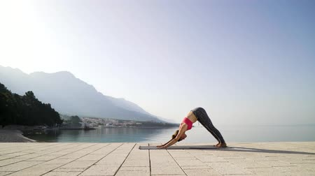 mozek : sporty woman doing yoga on seaside boardwalk with mountains on background
