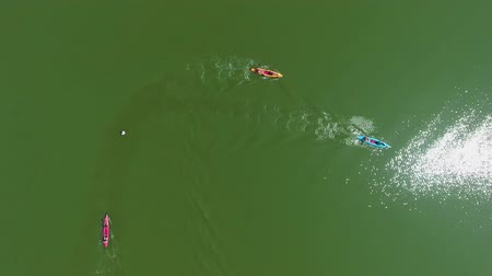 milestone : aerial top down of paddlers on colorful kayaks bypassing buoy at water race Stock Footage