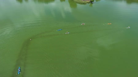 kano : aerial of water race with kayakers and stand up paddle boarders on green river