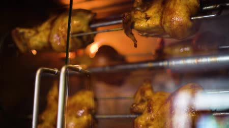 resistant : closeup rotisserie chicken grill rotating behind heat resistant glass door Stock Footage