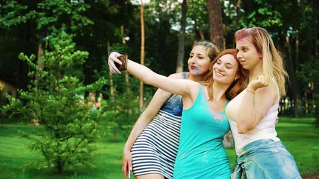 3 : three female friends in Holi paints make funny faces for selfie photo 動画素材