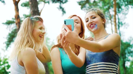 ziyafet : low angle of three young women in Holi paints take selfie photo on mobile