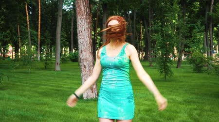 ziyafet : red haired young woman in wet dress and Holi paints laughs and jumps in park Stok Video