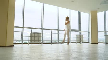 highheels : low angle shot of young blonde woman talking on phone in empty office lobby