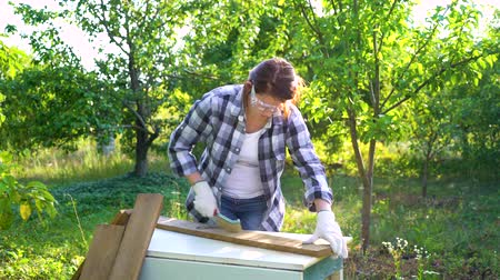 oprava : woman carpenter processing wooden plank with metal brush in garden
