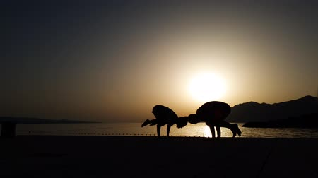 dark bay : silhouette of couple doing yoga at seaside at sunset with free space