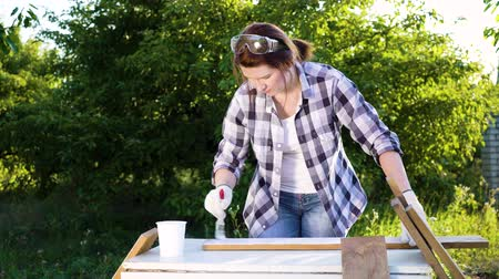 jeans short : adult crafts woman painting wooden planks with white paint in summer orchard Stockvideo