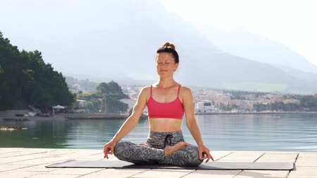 meditál : adult athletic woman meditates in lotus pose at seaside in morning sunshine Stock mozgókép