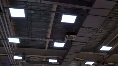 zinco : long pipes of hvac system and lamps hang on ceiling of big mall Filmati Stock