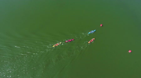 milestone : aerial top down of water race participants on kayaks bypass buoy on green river