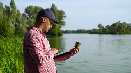 examinar : scientist ecologist examines green algae sample and enters data on tablet