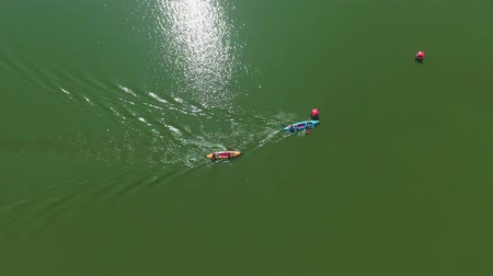 two seater : aerial top down water competition of people in two seater kayaks bypassing buoy Stock Footage