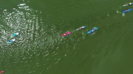 milestone : aerial top down of mixed race of kayakers and SUP boarders bypass buoy on water
