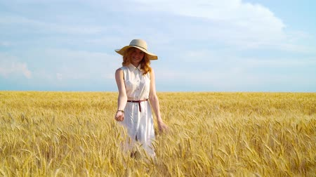 招待状 : following shot red haired woman in wheat field smiling and beckoning with finger