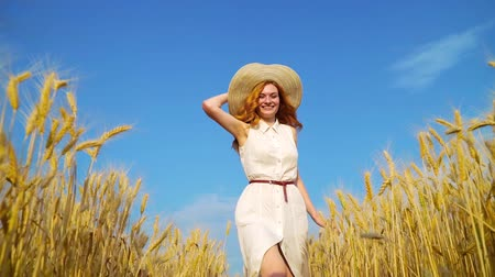 positive vibes : low angle shot of red haired woman walking towards moving camera in wheat field