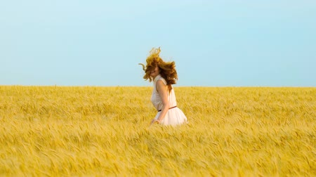positive vibes : young happy red haired woman jumping and running in wheat field in slow motion Stock Footage