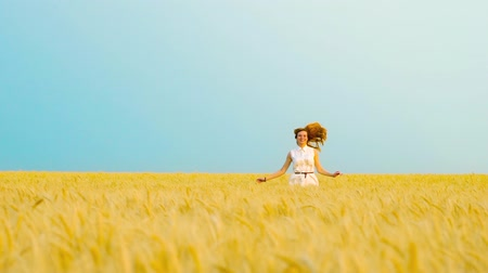 positive vibes : joyful red haired woman in white dress jumping in wheat field in slow motion Stock Footage